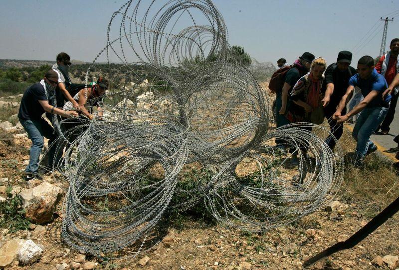 Palestinians&ForeignActivistsDamageWestBankFence