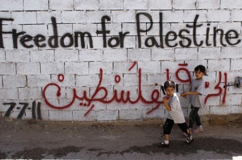 PalestinianGirlsWalkPastGraffitiAtDehaisheRefugeeCampInBethlehemReuters